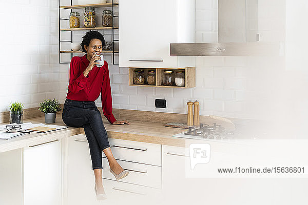 Smiling young woman sitting on kitchen counter at home drinking from mug