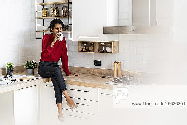 Lächelnde junge Frau sitzt zu Hause auf dem Küchentisch und trinkt aus der Tasse