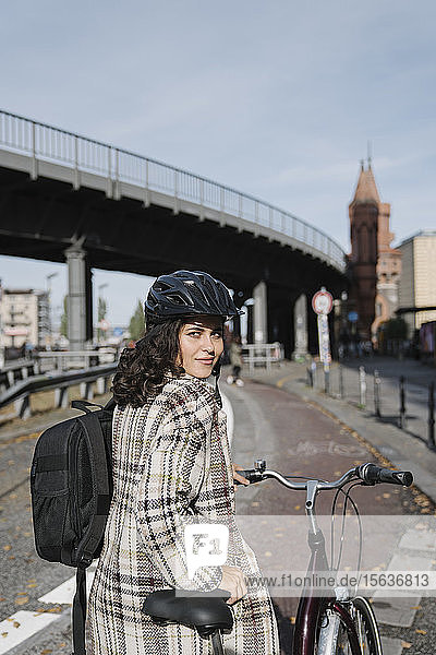 Portrait of woman with a bicycle in the city  Berlin  Germany