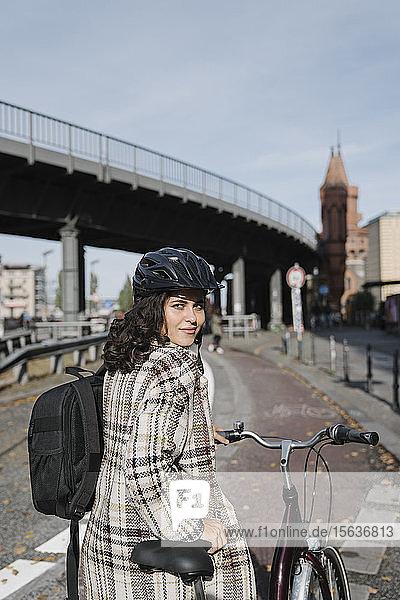 Porträt einer Frau mit Fahrrad in der Stadt  Berlin  Deutschland