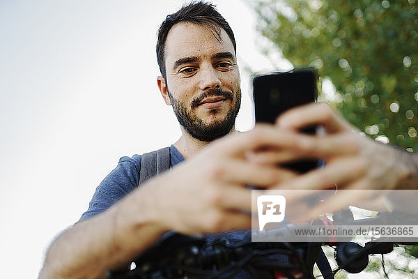Porträt eines zufriedenen Mannes mit Elektroroller beim Blick auf Handy