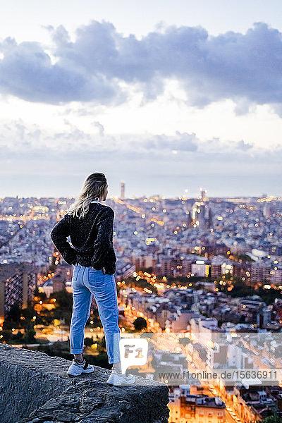 Rückansicht einer jungen Frau  die im Morgengrauen über der Stadt steht  Barcelona  Spanien