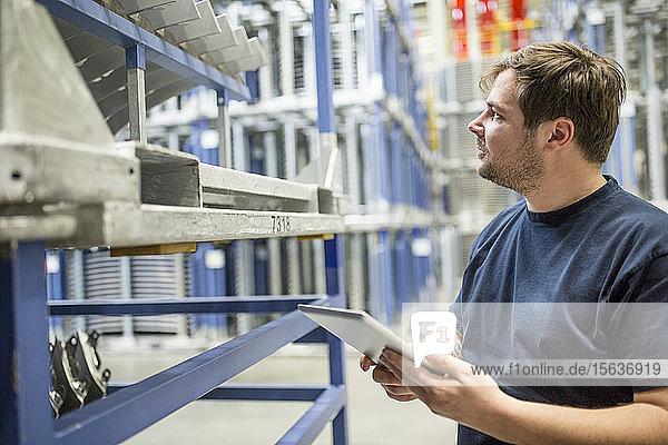 Arbeiter mit Tablette im Fabriklager