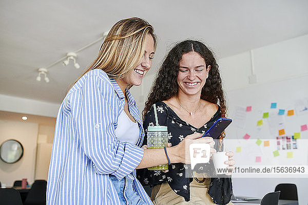 Happy casual young businesswoman showing cell phone to colleague in an office
