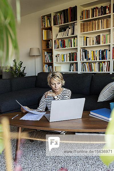 Reife Frau mit Dokumenten  die zu Hause einen Laptop benutzen