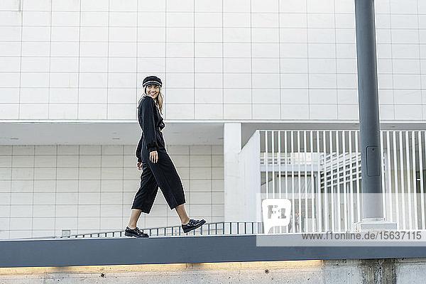 Junge blonde Geschäftsfrau mit schwarzer Matrosenmütze  die auf einer Mauer läuft