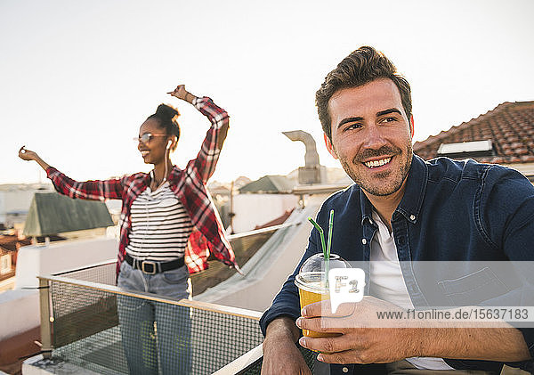 Glückliches junges Paar feiert eine Party auf dem Dach
