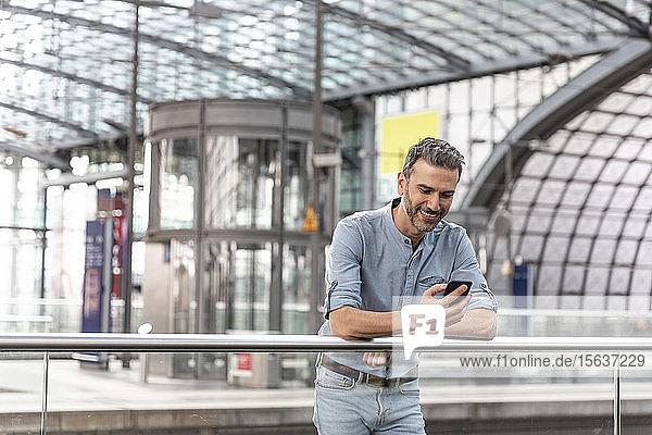 Lächelnder Mann am Bahnhof  der auf das Smartphone schaut