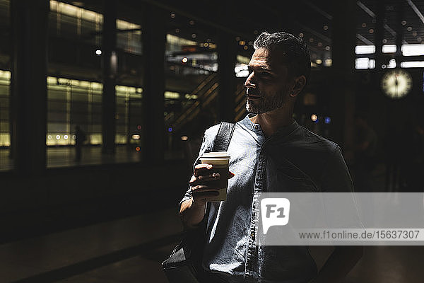 Man with takeaway coffee at the station in shadow