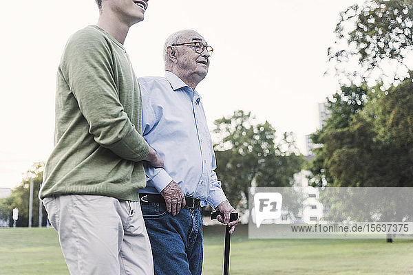 Senior man walking with help of his grandson in park