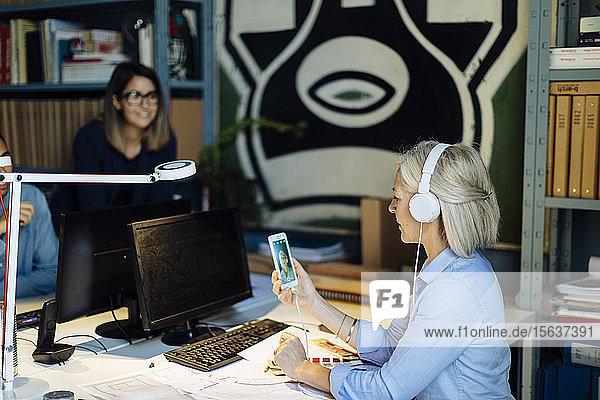 Reife Frau  die mit Kopfhörern telefoniert und im Architekturbüro sitzt