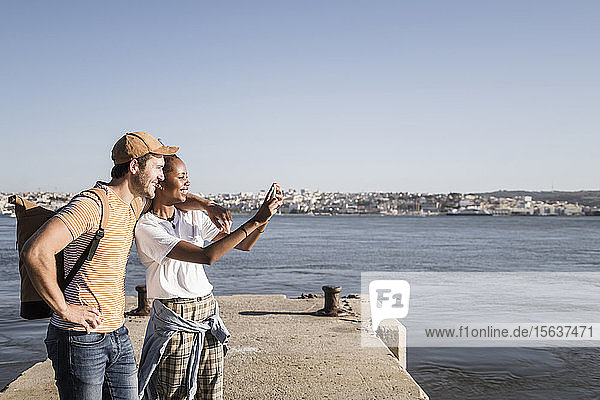 Happy young couple taking a selfie on pier at the waterfront  Lisbon  Portugal