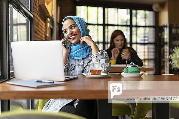 Geschäftsfrau  die in einem Café einen türkisfarbenen Hijab trägt und mit ihrem Laptop arbeitet  am Telefon