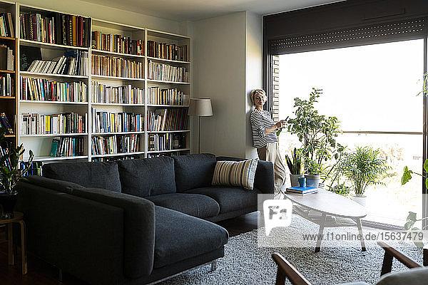 Reife Frau  die zu Hause am Fenster im Wohnzimmer steht