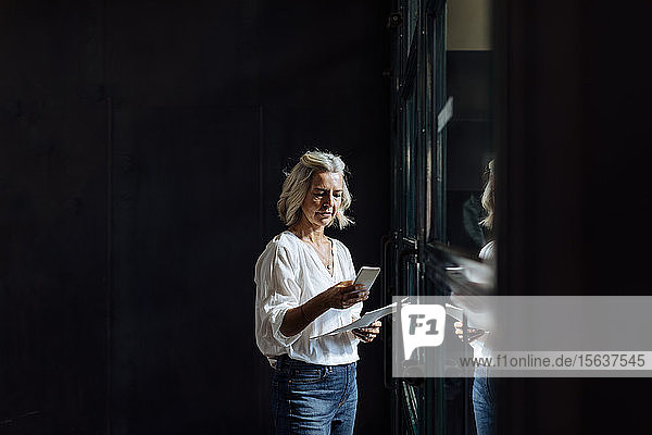 Casual mature businesswoman using smartphone at the window in loft office
