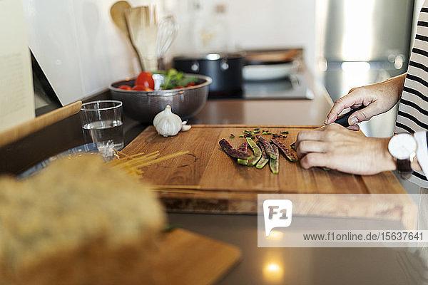 Nahaufnahme einer Frau  die zu Hause in der Küche kocht und Gemüse schneidet
