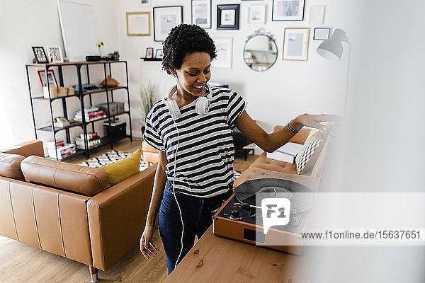 Young woman using record player at home