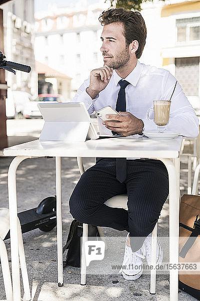 Junger Geschäftsmann mit Tablet und Mobiltelefon in einem Café in der Stadt  Lissabon  Portugal