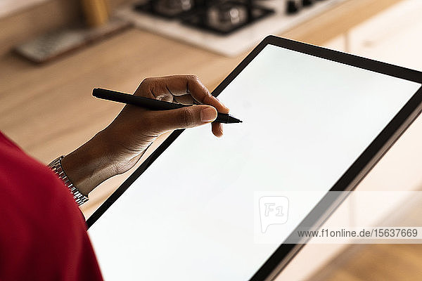 Close-up of woman using graphics tablet and stylus