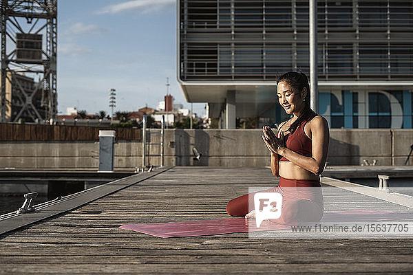 Asiatische Frau praktiziert Yoga  meditiert auf einem Pier am Hafen Asiatische Frau praktiziert Yoga, meditiert auf einem Pier am Hafen