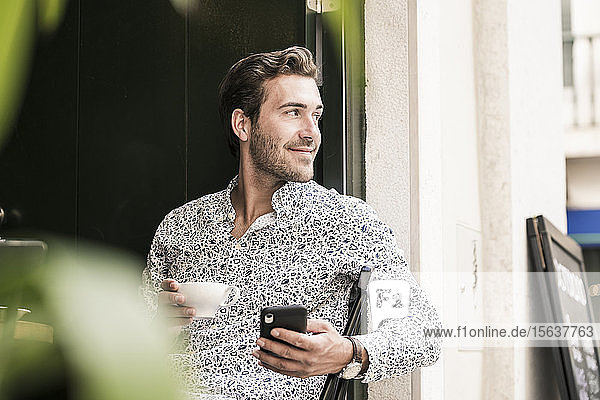 Young man with mobile phone having a coffee in a cafe in the city  Lisbon  Portugal