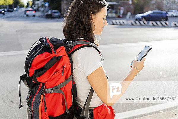Junge Rucksacktouristin mit rotem Rucksack mit Smartphone in der Stadt  Verona  Italien