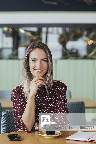 Porträt einer Frau  die in einem Cafe sitzt und Kaffee trinkt