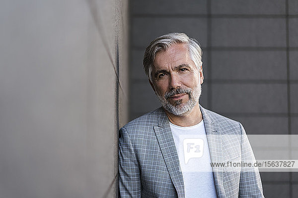 Portait of fashionable mature businessman leaning at a wall
