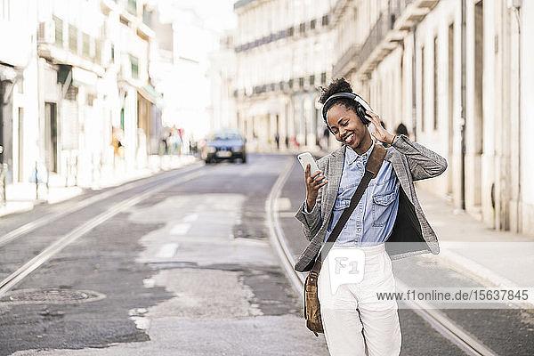 Glückliche junge Frau mit Kopfhörern und Mobiltelefon in der Stadt unterwegs  Lissabon  Portugal