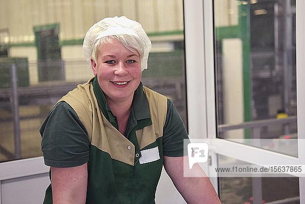 Portrait of female worker on conveyor belt in apple-juice factory