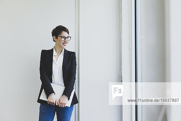 Smiling young businesswoman in office holding laptop