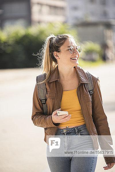 Junge Frau hält Smartphone und schaut zur Seite