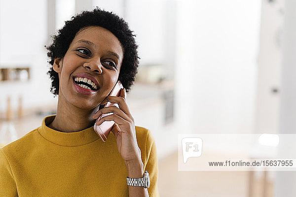 Glückliche junge Frau am Telefon zu Hause