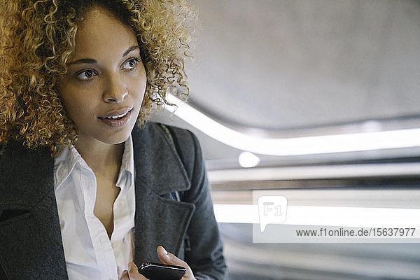 Porträt einer Frau mit Handy auf der Rolltreppe