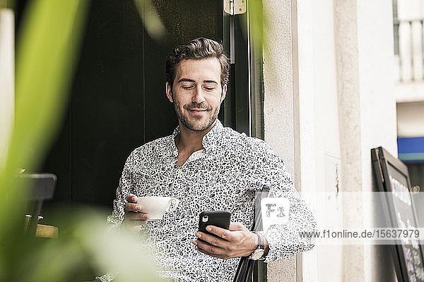 Junger Mann mit Mobiltelefon bei einem Kaffee in einem Café in der Stadt  Lissabon  Portugal