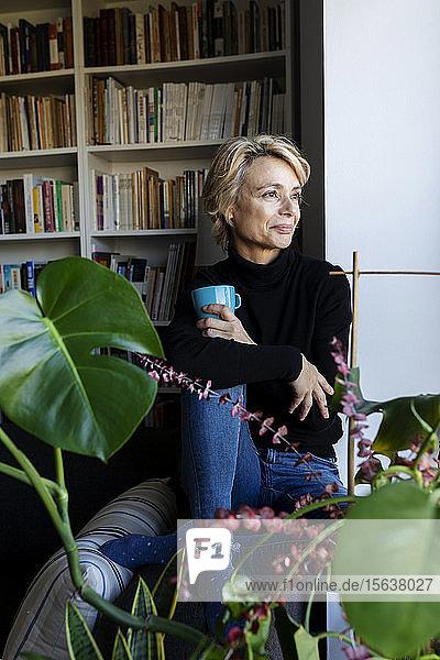 Reife Frau trinkt Kaffee und entspannt sich zu Hause