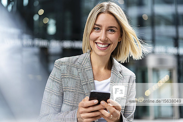 Porträt einer glücklichen jungen Geschäftsfrau mit Mobiltelefon in der Stadt