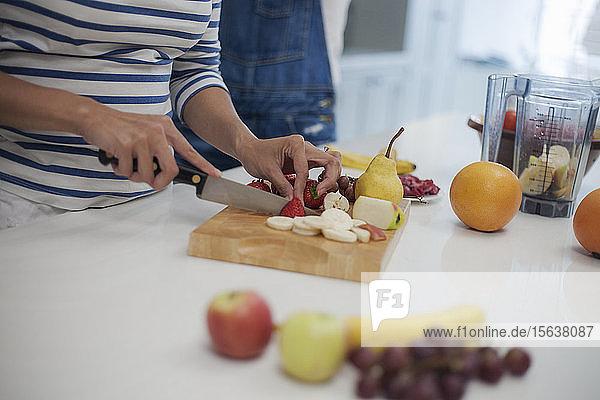 Frau hackt Früchte in der Küche  bereitet Smoothie zu
