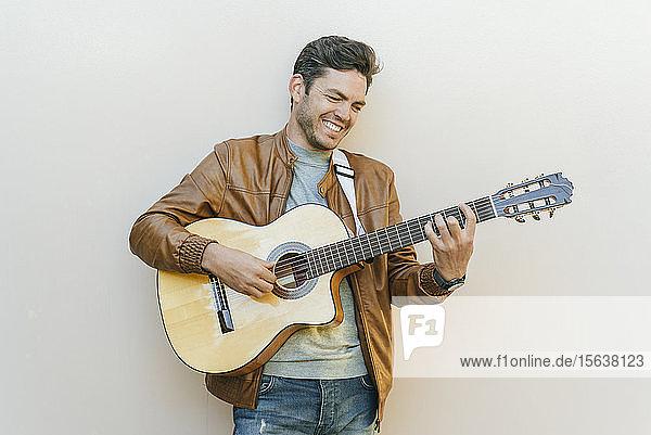 Lächelnder Mann spielt Gitarre vor einer Wand