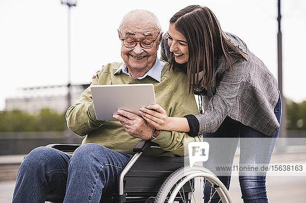 Älterer Mann sitzt im Rollstuhl und erwachsene Enkelin schauen gemeinsam auf das digitale Tablet