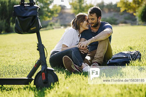 Glückliches Paar mit Elektroroller entspannt sich auf einer Wiese in einem Park