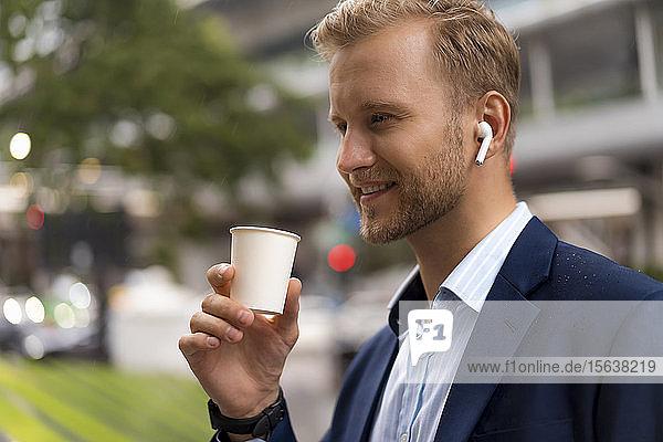 Junger lächelnder Geschäftsmann mit Kaffee zum Mitnehmen in der Stadt