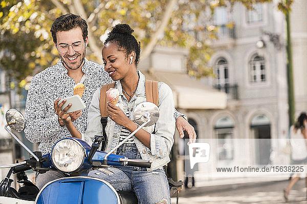 Lächelndes junges Paar mit Motorroller und Eiscreme per Handy in der Stadt  Lissabon  Portugal