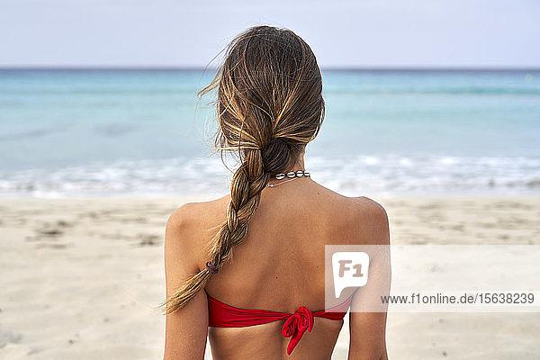 Rückansicht einer jungen Frau am Strand