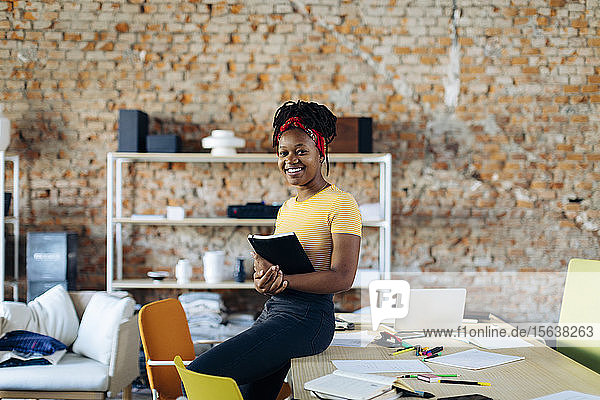 Portrait of confident young woman at table in office holding notebook