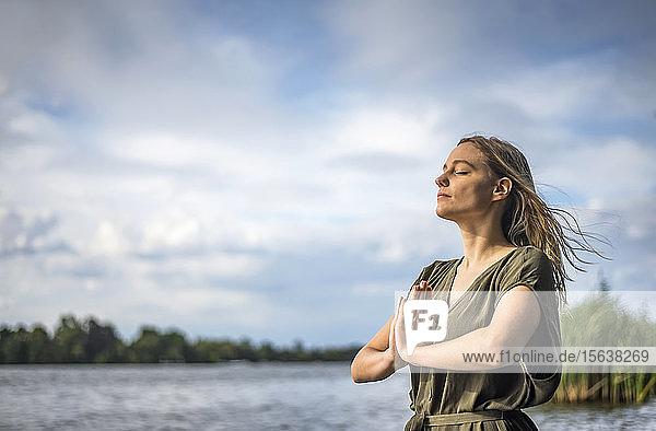 Frau meditiert an einem See