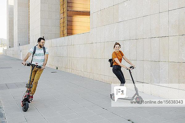 Ehepaar fährt Elektroroller auf dem Bürgersteig