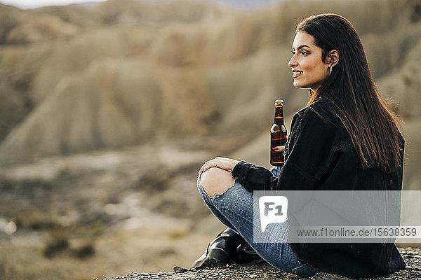 Junge Frau sitzt in Wüstenlandschaft und trinkt ein Bier  Almeria  Andalusien  Spanien