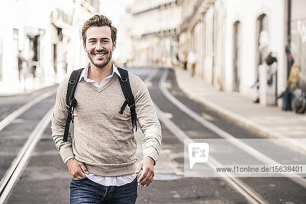 Porträt eines lächelnden jungen Mannes mit Rucksack in der Stadt unterwegs  Lissabon  Portugal