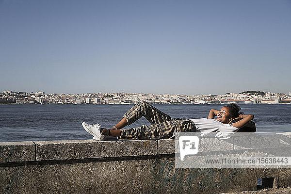 Junge Frau auf einer Mauer am Wasser liegend  Lissabon  Portugal